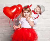 Little kids holding and picking up heart balloons. Valentine's D